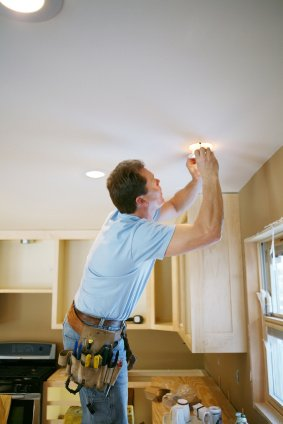 Electrician at work installing recessed lighting inside an Albany kitchen.